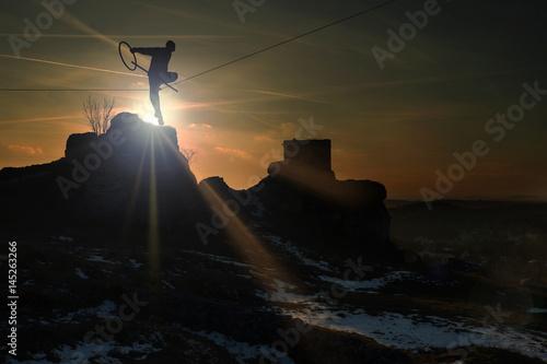 Valokuva  Człowiek na linie na zamku w Olsztynie o zachodzie słońca.