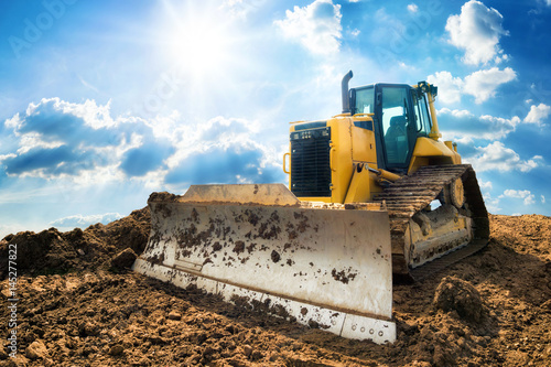 Fotografering Yellow excavator on new construction site, with the bright sun and nice blue sky