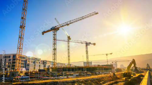 Fotografie, Obraz  Large construction site including several cranes working on a building complex,