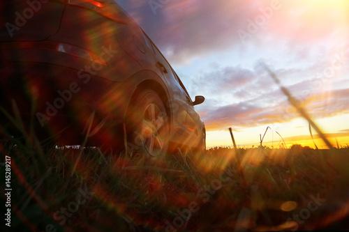 Foto auf Gartenposter Landschappen Car in the field at sunset