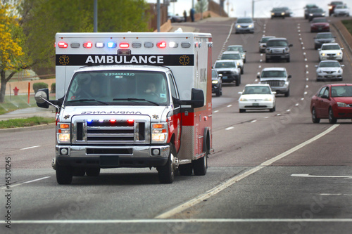 Ambulance with lights on driving down road Canvas Print