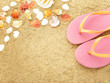 pink flip flops with sea shells on beach sand