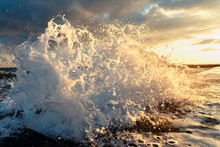 A Large Wave Breaks About A Breakwater Close-up Against A Sunset Background. Seascape