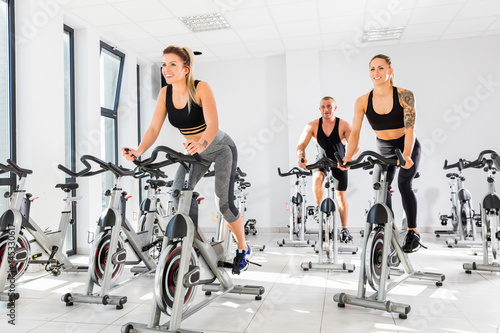Group of fit people training at spinning class. Wallpaper Mural