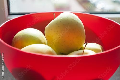 Fotografía  Green apples in red bowl