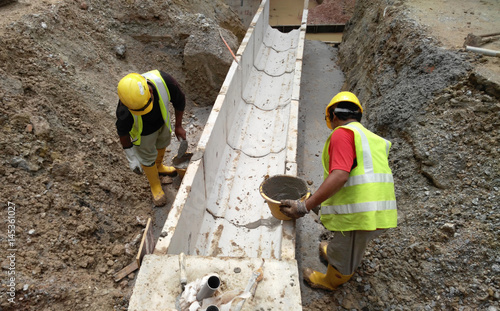 Fényképezés  Construction workers installing precast u-shape concrete drain at the construction site