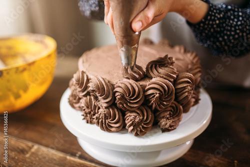 Fényképezés  Woman decorate cake with culinary syringe