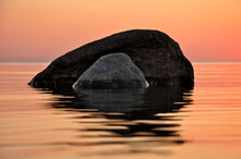 Large Stones In The Sea At Sunset.