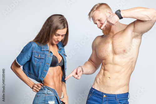 Fotomural  bearded muscular man shows perfect muscular abs of her sporty girlfriend sportsw