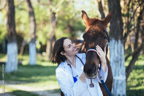 Photo  Vet petting a horse outdoors at ranch.