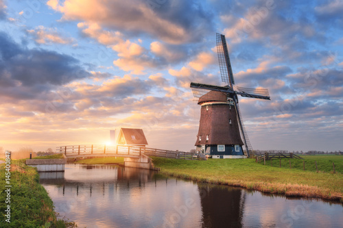 Valokuva  Windmill near the water canal at sunrise in Netherlands