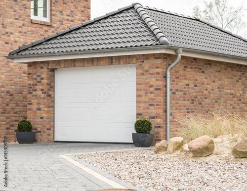 Fotografie, Obraz  Gemauerte Garage mit einem weißen Tor