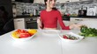 Young beautiful slender woman is cooking. Girl cuts vegetables for salad and smile