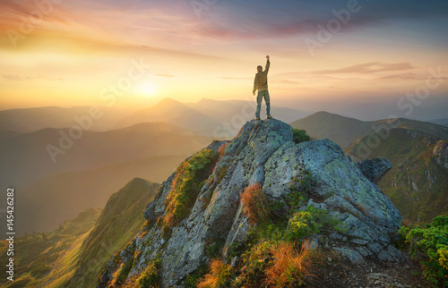 Foto auf Leinwand Bergsteigen Tourist on the peak of high rocks. Sport and active life concept