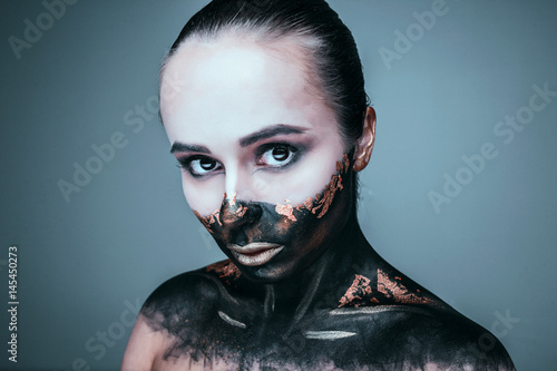 fashion portrait of a dark-skinned young girl with gold make-up.Beauty face. Picture taken in the studio on a grey and white background.