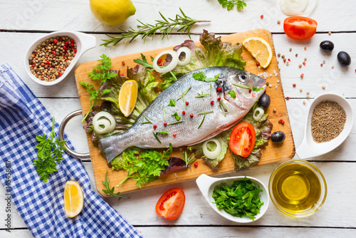 Keuken foto achterwand Vis Uncooked fish with herbs, lemon and spices on wooden cutting board