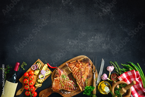 Aluminium Prints Grill / Barbecue Grilled T-bone steaks with fresh herbs and vegetables