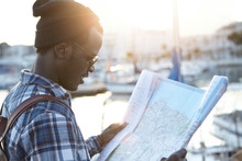 Youth And Travel Concept. Half-profile Portrait Of Dark-skinned Hipster-looking Tourist Just Arrived In Resort Town, Examining Paper City Guide, Learning Routes And Searching For Sightseeing