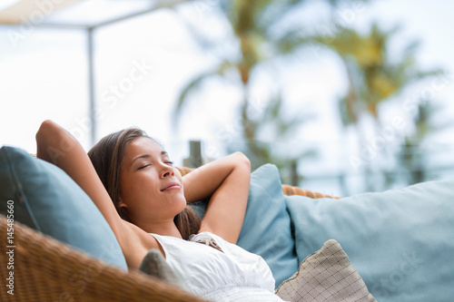 Deurstickers Ontspanning Home lifestyle woman relaxing sleeping on sofa on outdoor patio living room. Happy lady lying down on comfortable pillows taking a nap for wellness and health. Tropical vacation.