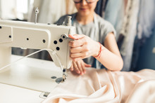 Closeup Portrait Of Young Woman Seamstress Sitting And Sews On Sewing Machine. Dressmaker Work On The Sewing Machine. Tailor Making A Garment In Her Workplace. Hobby Sewing As A Small Business Concept