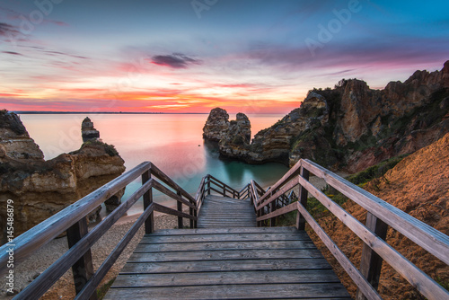 Carta da parati Wooden footbridge walkway to beautiful beach Praia do Camilo on coast of Algarve