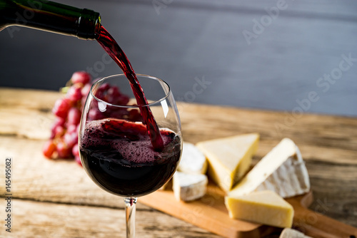 Foto op Aluminium Wijn Pouring red wine into the glass against wooden table