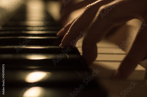 Fototapety, obrazy: Close-up soft focused atmospheric photo of a hand playing the piano keys. Concept: Music creating, composing, lyrics, performance