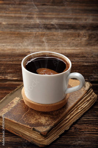 Spoed Foto op Canvas koffiebar Old book and cup of coffee on vintage wooden background