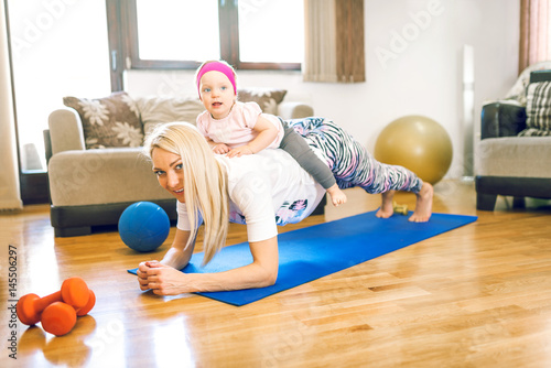 Fotografie, Obraz  Blonde mother doing fitness exercise with her baby daughter