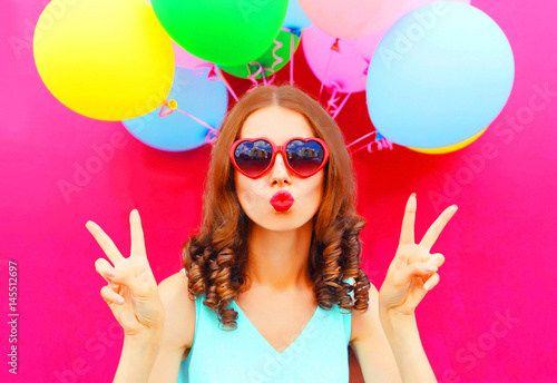 Photo  Fashion portrait woman blowing lips holds an air colorful balloons on a pink bac