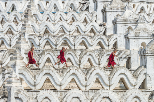 Three young monk are running and jumping on the Mya Thein Tan Pagoda at bagan, m Poster