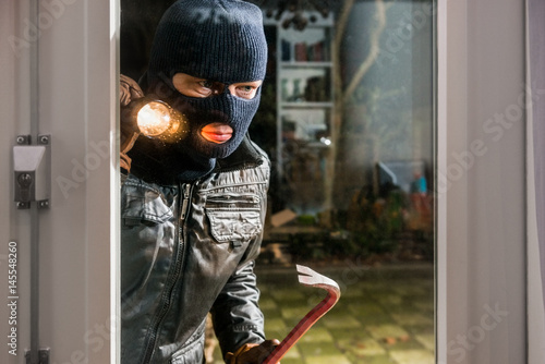 Fotomural  Masked burglar with flashlight and crowbar looking into glass window of house