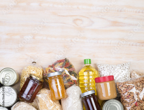 Spoed Fotobehang Eten Food donations on wooden background, top view with copy space