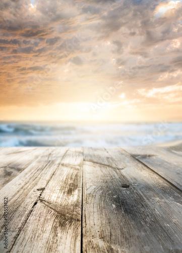 Foto-Schiebegardine Komplettsystem - Wooden table and sunset at seaside. Focus on table, blurred background. (von Sergey Peterman)