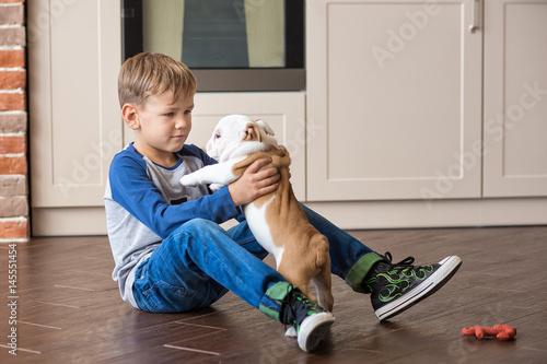 Fotografie, Obraz  Cute boy playing with puppy english bulldog