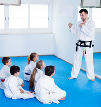 Male Coach Explaining New Maneuvers To Children