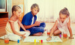Boy and two girls playing at board game indoors