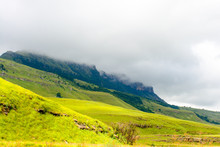 Color Panorama Scenic Landscape Photo Of South Africa Drakensberge Scenic Nature, Green Plane And Mountains In Dense Clouds With Rocks And Bushes On A Sunny Day