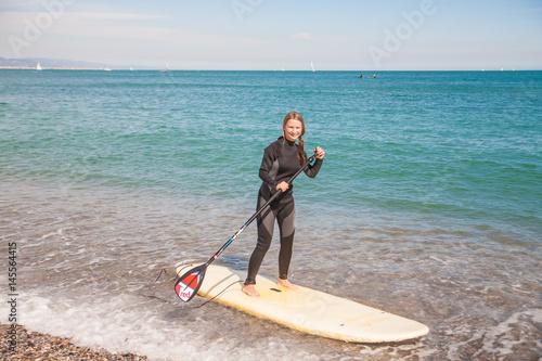 Plakat Młoda kobieta w kombinezon pływać na wstać pokładzie wiosła
