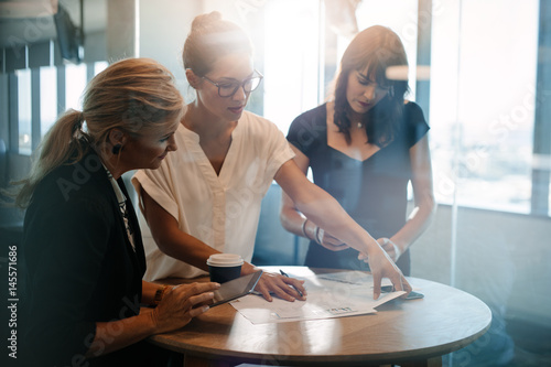 Obraz Female colleagues having a standing meeting around table - fototapety do salonu