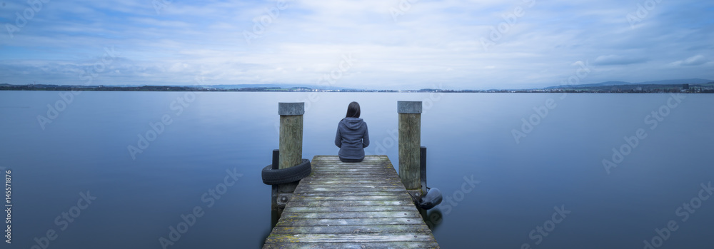 Fototapety, obrazy: Overcast. Self reflection in magical world of fantasy. One woman sits on a wooden pier. Cloudy above the lake. Long exposure.
