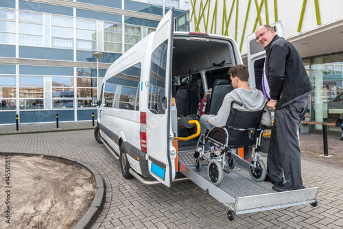Leinwand Poster Driver Assisting Passenger In Wheelchair To Board Taxi