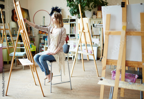 Serious girl sitting in front of easel and drawing Canvas Print
