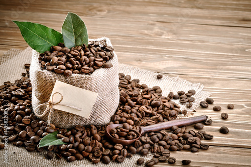 Salle de cafe Bag of burlap filled with coffee beans on wooden background.