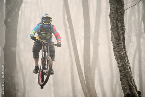 Photo A mountain bike rider jumps from a springboard in a foggy forest, in the Caucasu
