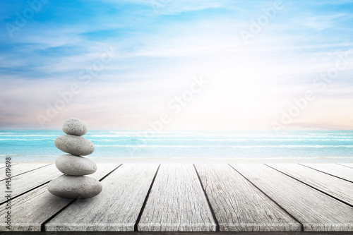 Fotobehang Zen Stack of pebble stones at the beach on a wooden surface. Concept Zen, Spa, Summer, Beach, Sea, Relax.