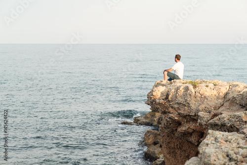 Fotografía  Hombre joven sentado al borde de un acantilado al atardecer