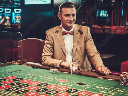 Upper class man gambling in a casino плакат