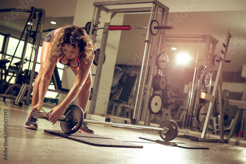 Poster  Woman in late 30s setting weights on barbell in gym before weightlifting