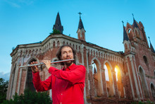 Musician In Red Playing The Flute Near An Old Castle At Sunset